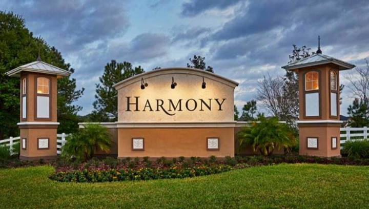 Harmony Main Entrance Sign & Towers with Landscaping in the foreground & Sky in the background